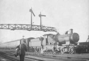 An unidentified GW Bulldog 4-4-0 passes under the signal gantry at Abbey Foregate, whilst some railway official is probably coming from the signal box.